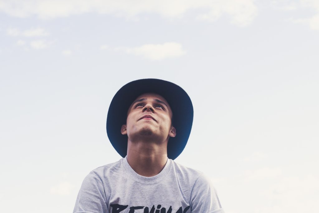 Teenager with hat looking up to sky
