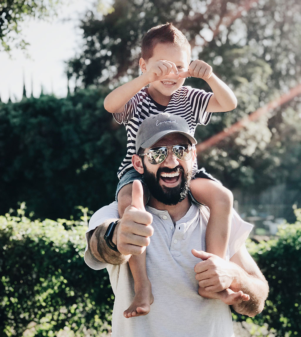Man with beard with young boy on his shoulders