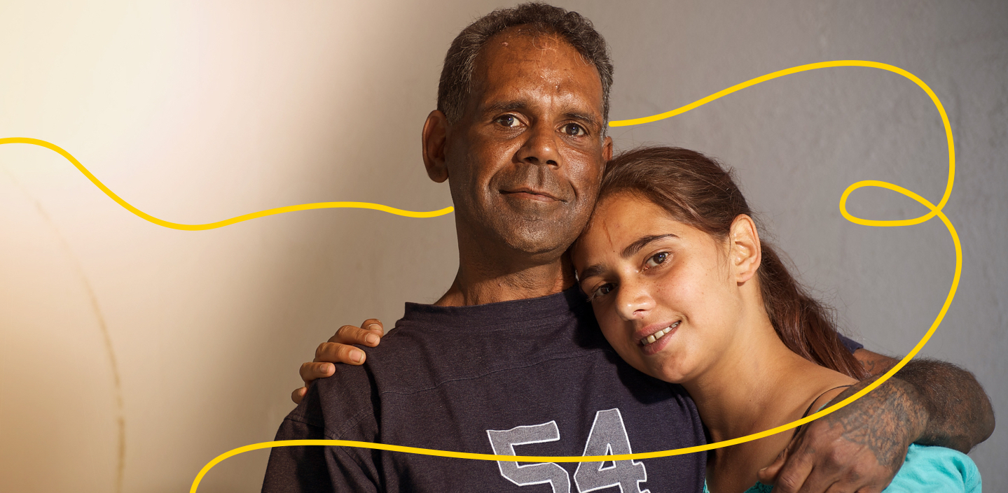 Indigenous Australian man with his adult daughter against a grey background